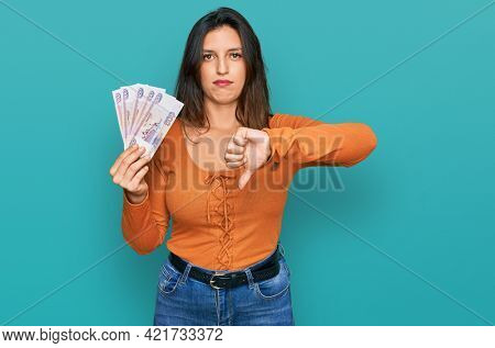Beautiful hispanic woman holding russian 500 ruble banknotes with angry face, negative sign showing dislike with thumbs down, rejection concept
