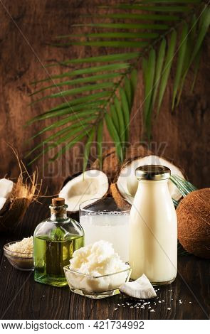 Coconuts Products - Mct Butter, Oil, Milk, Shavings On Wooden Table Background. Hair, Skin And Body