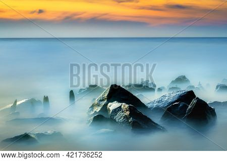 Rocky Coast Of Sea. Slow Shutter Speed For Smooth Water Level And Dreamy Effect