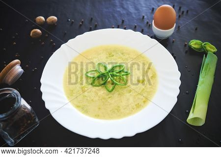 Vegetable Pork Soup In A White Plate On A Black Background With A Still Life With Pepper, Nutmeg, Le