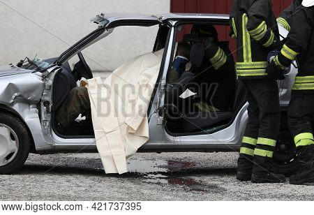 Fire Brigade Team During The Rescue Of The Injured Person After The Car Accident And The Wrecked Car