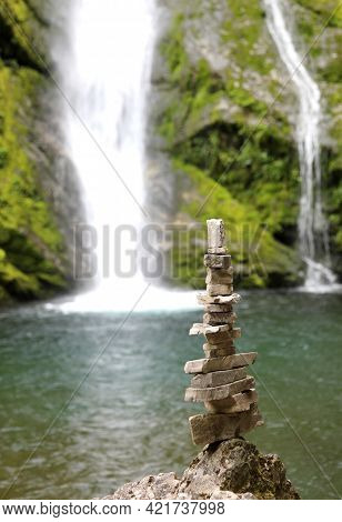 High Pile Of Stones Near A Waterfall In The Mountains Called Cairn Or Little Man By Mountaineers