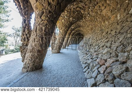 BARCELONA, SPAIN - MARCH 22, 2019: Park Guell by Antonio Gaudi. Stone colonnade resembling tree trunks by Antonio Gaudi in Park Guell, Barcelona. Spain