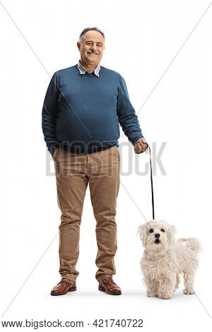 Full length portrait of a happy mature man holding a maltese poodle dog on a lead isolated on white background
