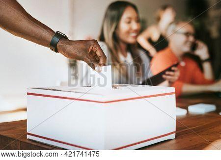 Black man casting his vote to a ballot box