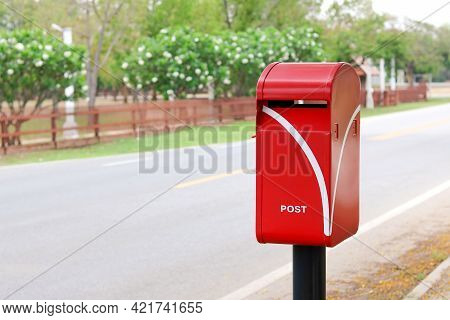 A Red Post Box Is On The Roadside.