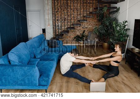 Sporty Young Couple Warming Up Stretching Watching Fitness Video Tutorial Online On Laptop, Fit Man