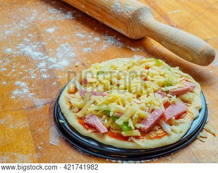 Pizza With Pieces Of Meat, Green Pepper And Cheese On A Wooden Table Sprinkled With Flour. Nearby Is