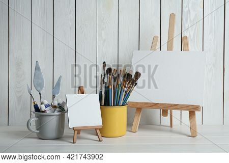 Easels With Blank Canvases, Paints And Brushes On White Wooden Table
