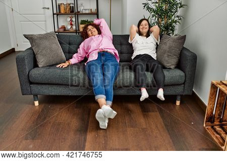 Mature mother and down syndrome daughter at home resting on the sofa