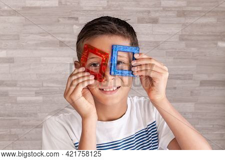 Child Plays With A Magnetic Constructor. Boy Playing With Colorful Toy Blocks. Boy Put The Details O