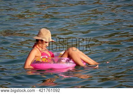 Kusadasi, Turkey - May 2021: Girl In Pink Swimsuit And Hat Looks At Her Breasts While Swimming In