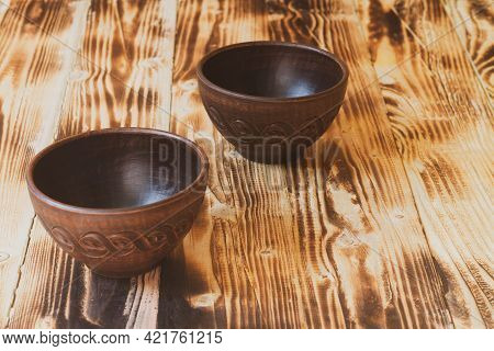 Two Empty Earthenware Bowls On A Brown Wood Table.