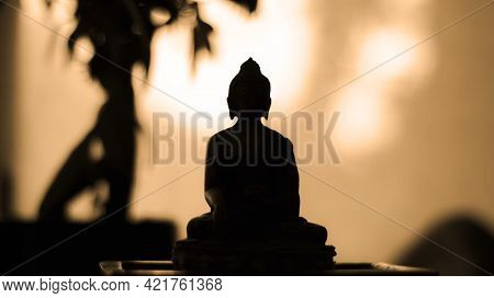 Backlight Silhouette Of Meditating Buddha Statue At Sunset - Bokeh Background - Warm Colors