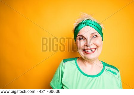 Portrait Of Happy Smiling Elderly Woman In Sports Armband And T-shirt Standing Against Yellow Backgr