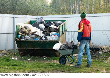Young Man Takes Out Garbage In A Wheelbarrow At Countryside In Cold Spring Evening