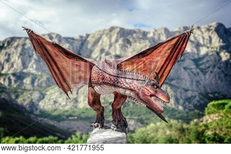 Dragon Sitting On A Rock. Ancient Lizard Or Dragon On The Background Of Rocky Mountains.