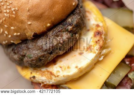 Bun With Grilled Meat, Scrambled Eggs And Cheese. Cheeseburger, Close Up Shot. Junk Hearty Food. Hor