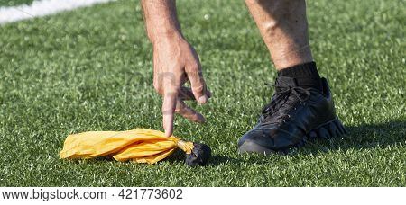 A Game Referees Hand Picking Up The Yellow Penalty Flag That Was Thrown During The Game.