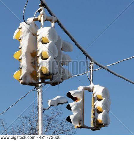 Dangerous Conditions With Traffic Lights Covered In Snow After A Snowstorm With Deep Blue Sky In The