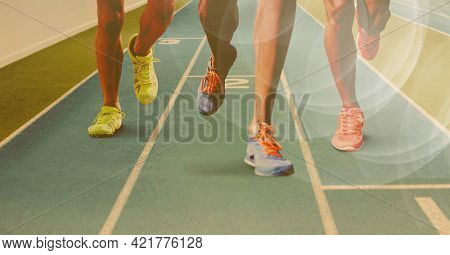 Composition of legs of running athletes on racing track with spots of light. sport and competition concept digitally generated image.