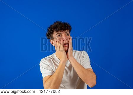 Attractive Young Man With Curly Hair With Hands On Face With Scared Gesture Isolated On Blue Studio