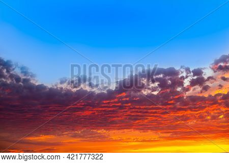 Bright Contrasting Dramatic Sky With Clouds At Sunset. Saturated Colors Orange And Blue.