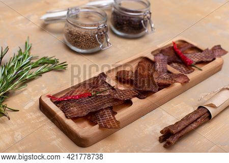 Jerky Snacks On Wooden Board, Red Papper, Meat Sticks, Peppercorns In Glass Jars And Rosemary On Lig