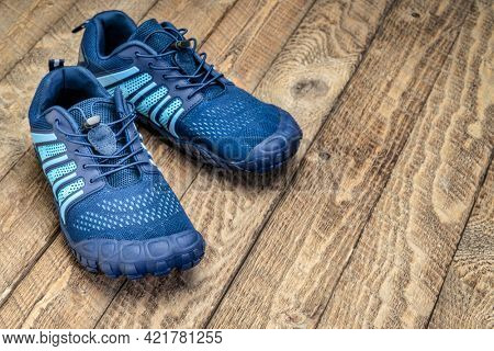 barefoot cross training and running shoes on rustic wooden background