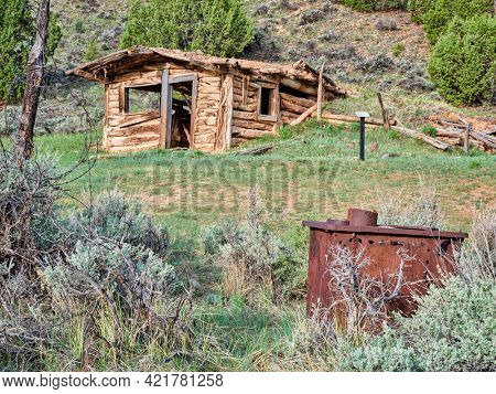 rusty oven and a small, old, log cabin sits on a hillside surrounded by grass - Baker Cabin above Yampa River in Dinosaur National Monument in Colorado