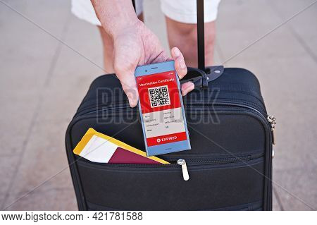 Open Suitcase And Smartphone In Hand Displaying On App Mobile Expired Digital Vaccination Certificat