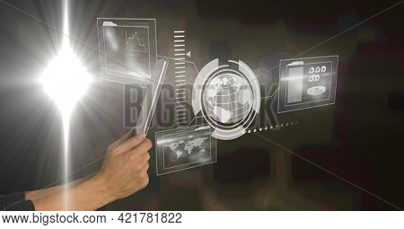 Hands holding tablet and digital interface with globe map and information on dark background. global communication technology digital interface concept, digitally generated image.