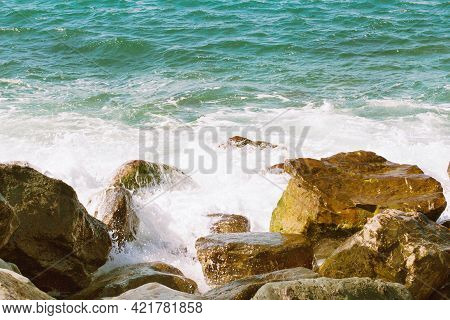 Turquoise Waves Crash Against Brown Stones On The Seashore