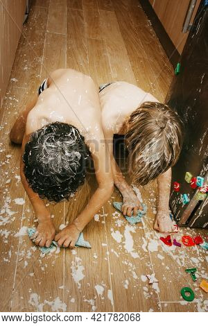 Two Kids Cleaning Up After A Flour Fight. Positive Punishment For Kids Concept. Childen Mischief