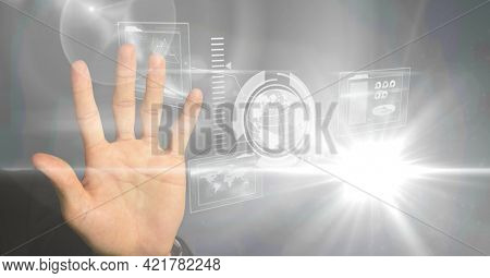 Hand using digital interface screen with network of icons, globe and charts. global business, digital interface and communication technology concept, digitally generated image.