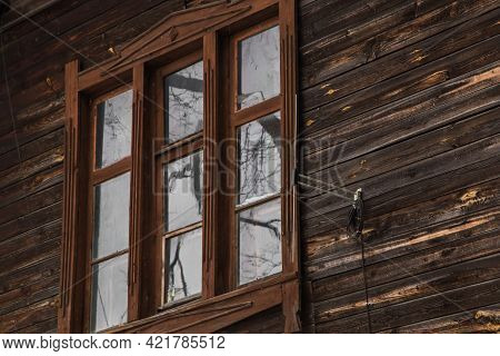 A Wooden Window In An Old Planked Building With An Antenna On The Wall. An Old Wooden Building In Th