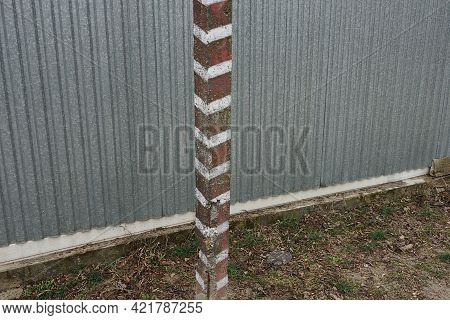 One Iron Striped Boundary Post Stands On The Street Against A Gray Metal Wall Of The Fence