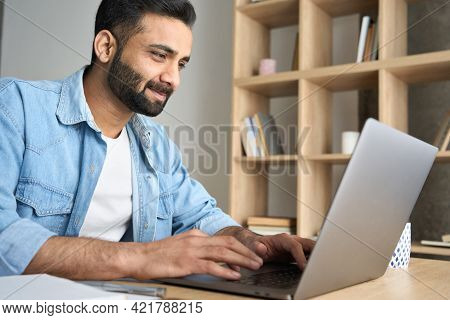Handsome Young Indian Hispanic Businessman Using Computer Working Remotely From Modern Home Office.