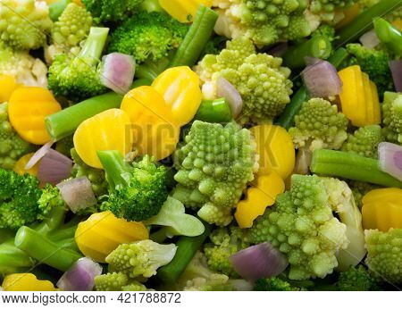 mix of various vegetables like broccoli, romanesco broccoli, yellow carrot slices, green beans and red onion pieces