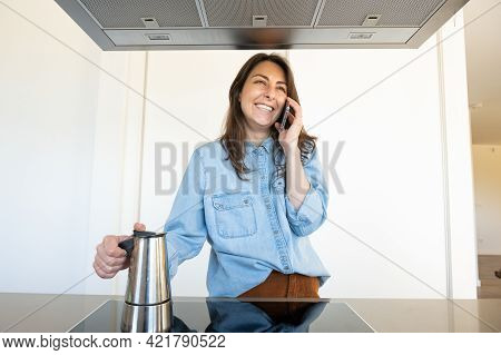 Smiling Young Woman Talking On The Phone In The Kitchen Of Her Home While Holding A Coffee Maker