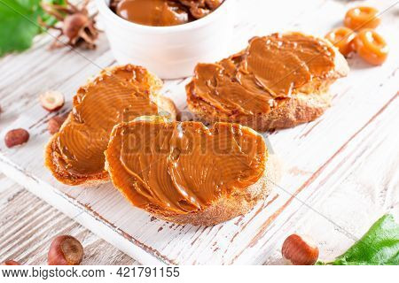 Slices Of Bread With Chocolate Nut Cream Or Boiled Condensed Milk On A Cutting Board On A Wooden Bac