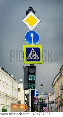 City, Street, Pillar With Few Road Signs And Traffic Light Close-up