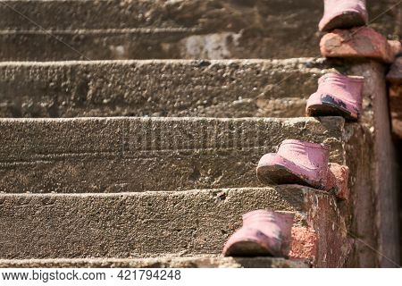 Rubber Galoshes, Painted Pink, Are Displayed One After The Other On The Steps Of The Concrete Stairc
