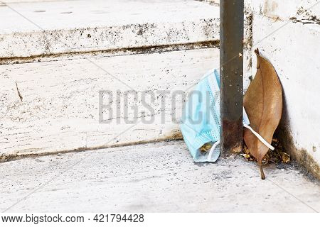 Surgical Masks Discarded On The Street. Protective Mask Used Is On The Step Next To A Dry Sheet Of F