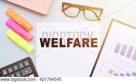 The Text Welfare On Office Desk With Calculator, Markers, Glasses And Financial Charts.