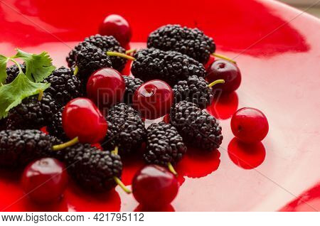 Ripe Large Black Mulberries And Red Cherries On A Red Plate, Close-up.