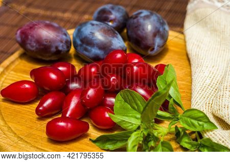 Still Life - Fresh Large Dogwood Berries, Purple Plums And A Sprig Of Basil On A Wooden Board