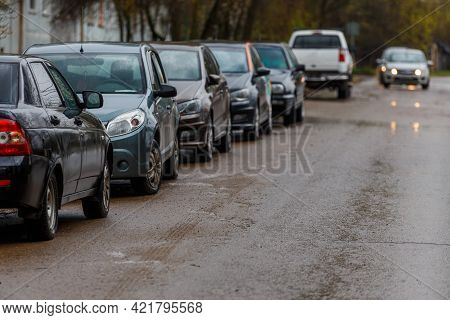 Cars Parked On Side Of Wet Dirty Road - Telephoto Close-up With Selective Focus