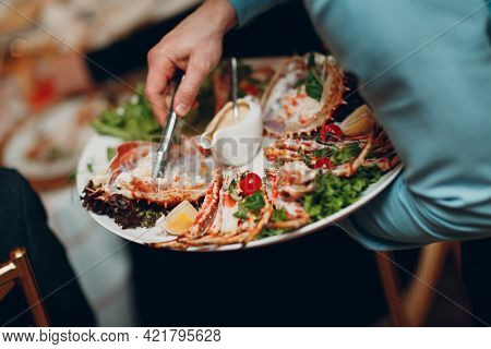 A Waiter In A Restaurant Holds Seafood Dishes And Serves A Table Catering Concept Healthy Food Octop