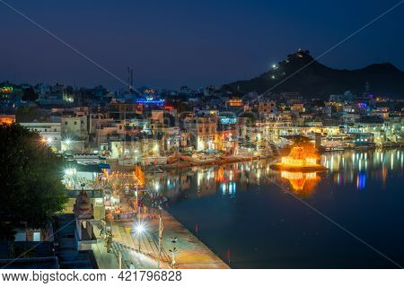 View of famous indian hinduism pilgrimage town sacred holy hindu religious city Pushkar with Brahma temple, aarti ceremony, lake and ghats illuminated at sunset. Rajasthan, India. Horizontal pan